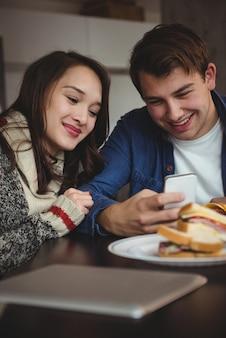 Casal usando telefone celular enquanto toma o café da manhã