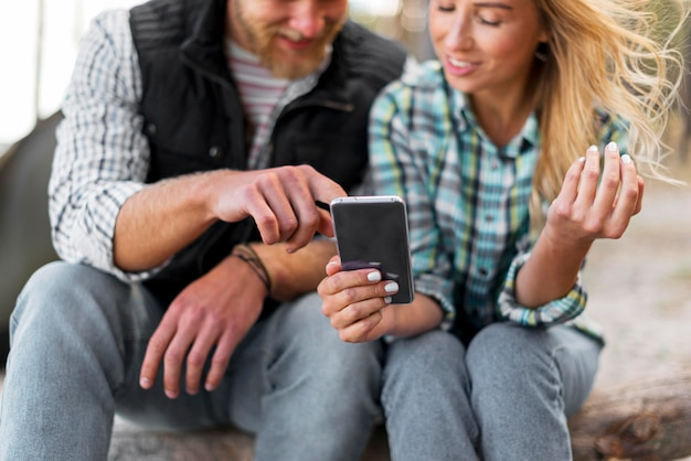 Casal usando telefone celular na natureza