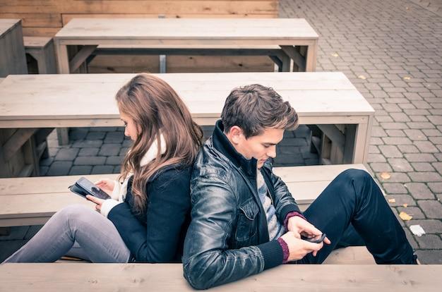 Casal usando telefone móvel esperto na fase comum moderna de desinteresse mútuo