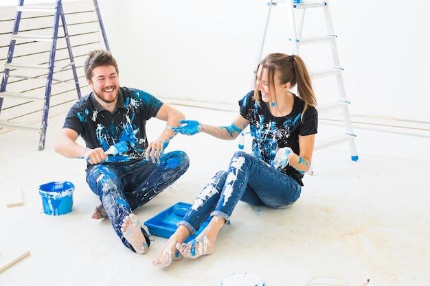 Casal vai pintar a parede, estão misturando a cor e se divertindo
