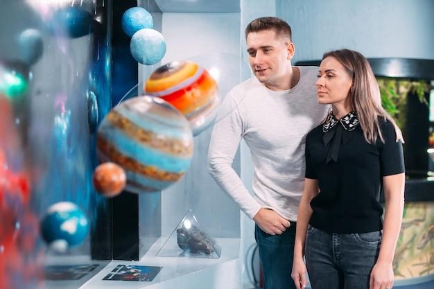 Casal vê a exposição dos planetas do sistema solar no museu