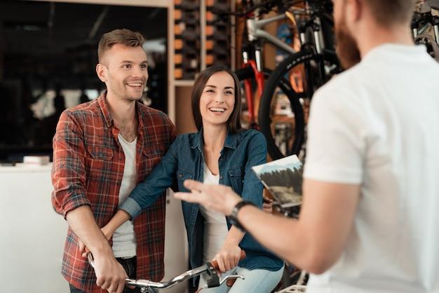 Casal veio à loja de bicicletas para escolher uma bicicleta nova