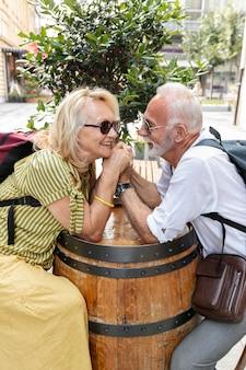 Casal velho feliz, segurando as mãos em um barril