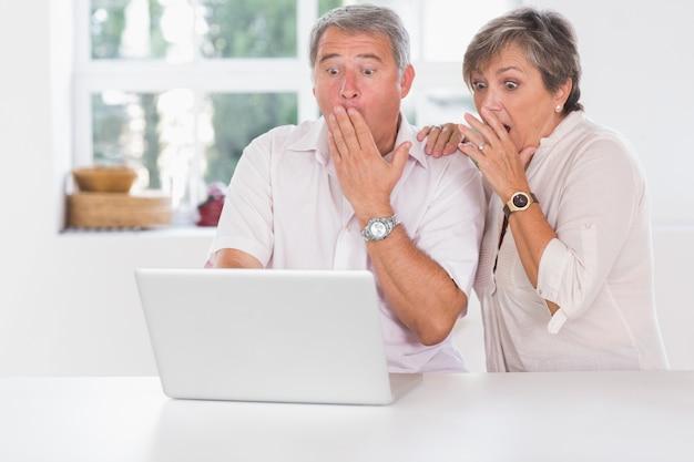 Casal velho surpreendido na frente de um laptop