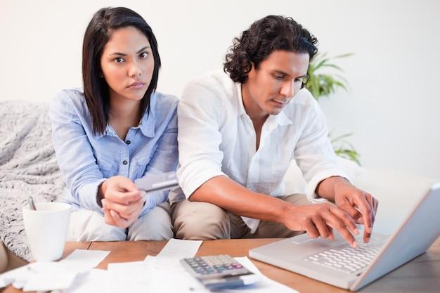 Casal verificando suas contas bancárias on-line na sala de estar