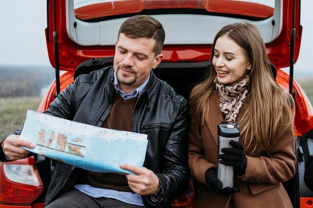 Casal verificando um mapa no porta-malas do carro