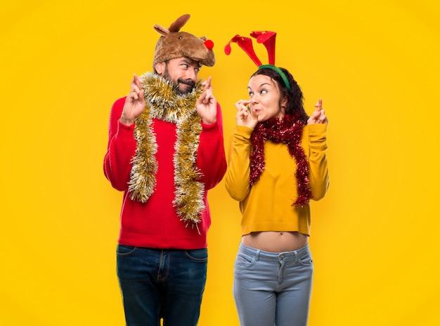 Casal vestido para as férias de natal com os dedos cruzando e desejando o melhor