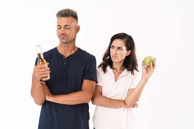 Casal vestindo roupa casual em pé, isolado na parede branca, homem feliz segurando uma garrafa de cerveja, mulher zangada segurando uma maçã verde