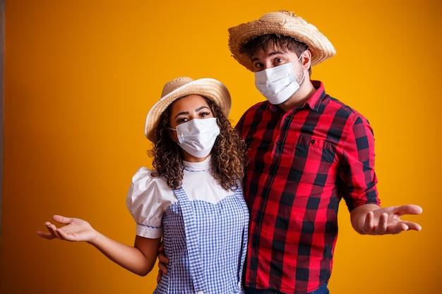 Casal vestindo roupas típicas de festa junina e máscara de proteção para evitar covid-19