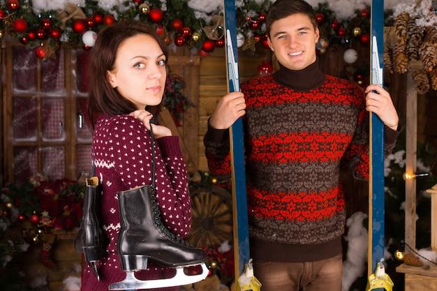 Casal vestindo suéteres segurando patins e esquis em frente à cabana de madeira no inverno