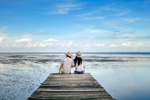 Casal viajante à procura de vista da floresta de mangue e o mar de férias