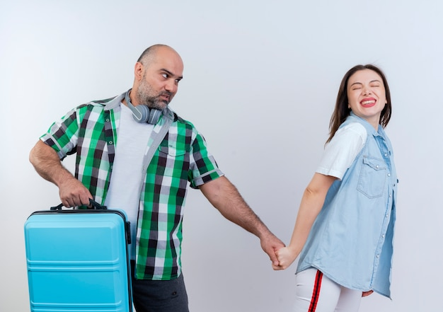 Casal viajante adulto usando fones de ouvido no pescoço segurando uma mala