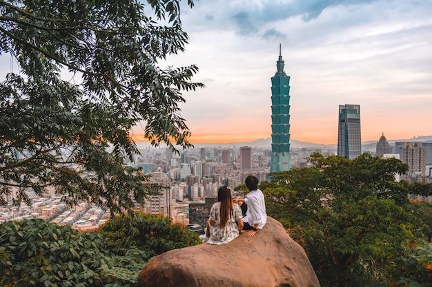 Casal viajante e pôr do sol com vista do horizonte da paisagem urbana de taipei taipei 101 edifício da cidade financeira de taipei, taiwan