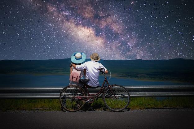 Casal viajante sentado perto de uma bicicleta e olhando para a via láctea e estrelas no céu
