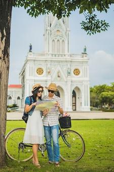 Casal viajante usando um mapa local fundo é bela igreja.
