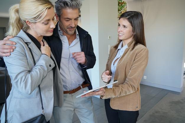 Casal visitando casa com agente imobiliário