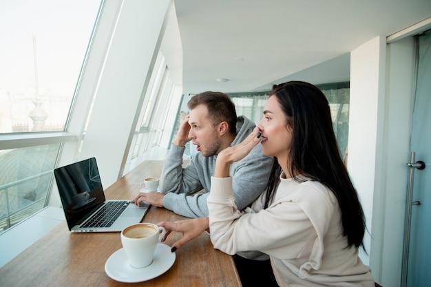 Casal viu algo disparando no laptop. homem brinca com o cabelo e a mulher ri e cobre a boca com a mão. xícara de café vazia. sala de luz branca no fundo.
