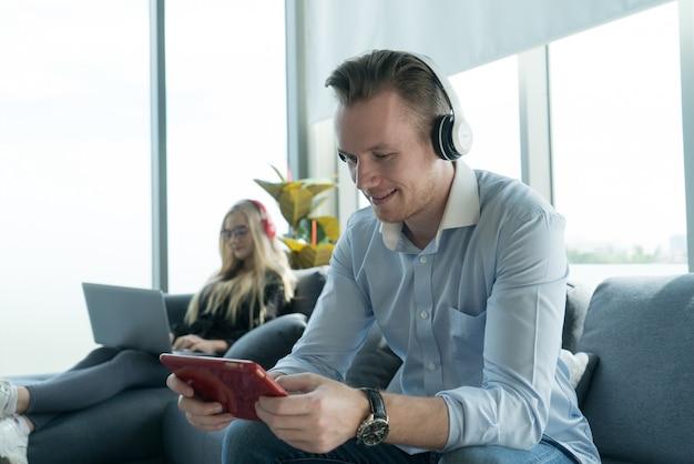 Casal yung com aparência casual aprecia a rede social e jogar o jogo do tablet fica junto em casa.