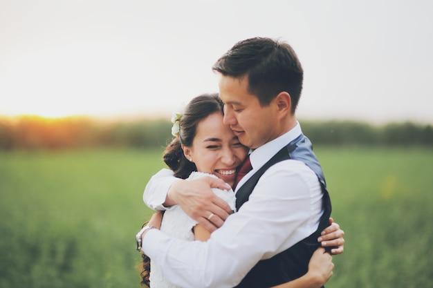 Casamento. a noiva e o noivo se abraçam no parque ao pôr do sol