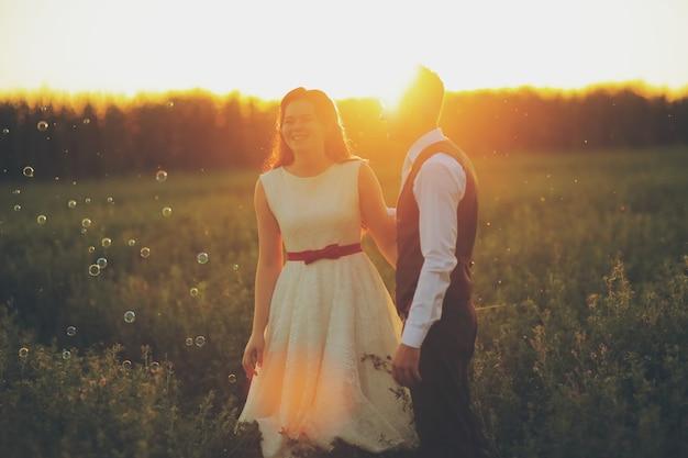 Casamento. a noiva e o noivo se dão as mãos e caminham no parque sob a luz do sol