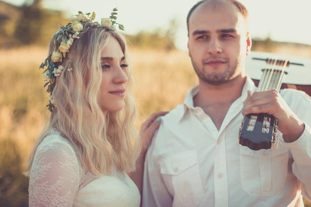 Casamento ao ar livre em estilo piquenique noivo tocando violão jovem blomde noiva no pôr do sol de verão