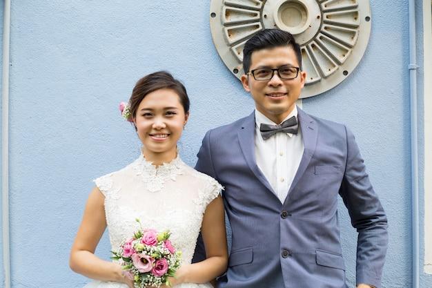 Casamento asiático segurando uma flor e procurando a câmera no jardim.