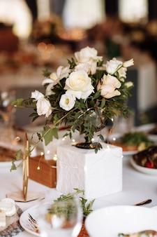 Casamento. banquete. a mesa festiva para noivos, noivos e convidados, decorada com uma composição de flores brancas e rosa e folhagens, existem velas, servidas com louças em restorane.