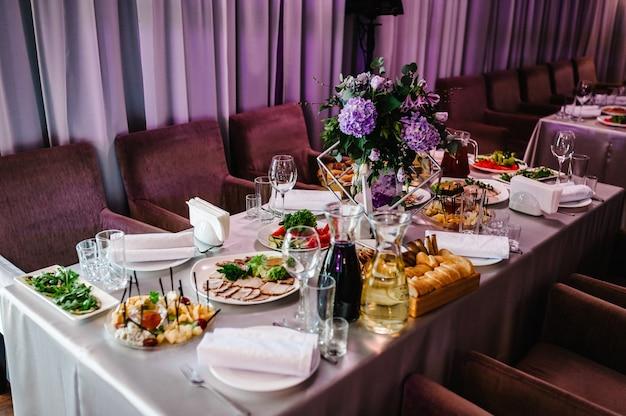 Casamento. banquete. as cadeiras e mesa para convidados, servidas com talheres, flores e louças e cobertas com toalha de mesa. configuração de casamento. decoração.