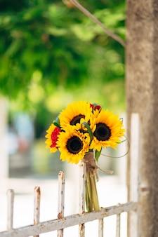 Casamento bouquet de noiva de girassóis em uma cerca de metal casamento