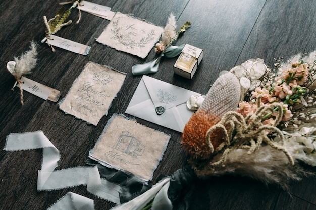 Casamento buquê artes rústicas e gráficas de cartões de caligrafia linda com bobinas de flores e chiffon na mesa de madeira. convite de casamento lindo. vista do topo.