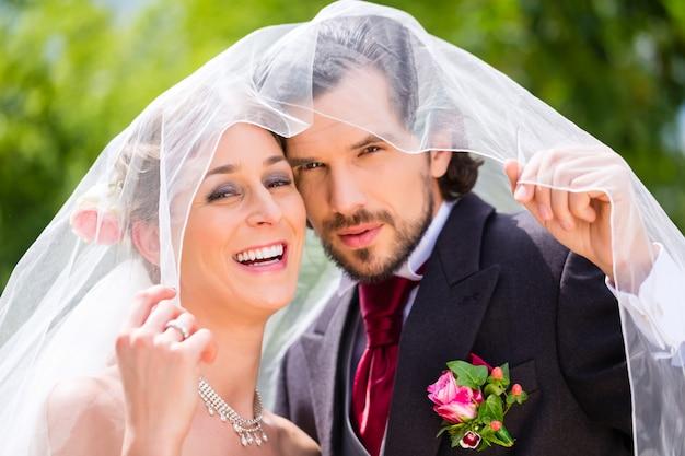 Casamento casal noiva e noivo escondido sob o véu