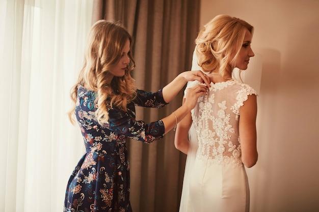 Casamento. dama de honra preparando a noiva para o dia do casamento. a dama de honra ajuda a fechar o vestido antes da cerimônia.