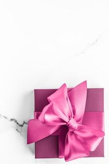 Casamento de aniversário e conceito de marca feminina caixa de presente rosa com laço de seda no fundo de mármore presente de chá de bebê feminino e presente de moda glamour para design de arte plana de luxo de beleza de marca