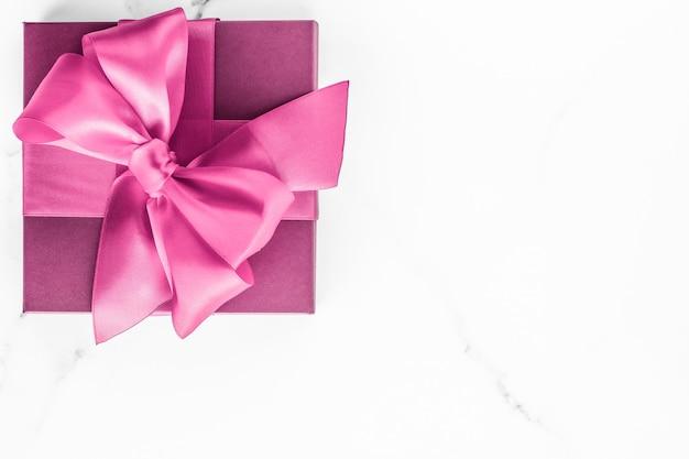 Casamento de aniversário e conceito de marca feminina caixa de presente rosa com laço de seda no fundo de mármore presente de chá de bebê para meninas e presente de moda glamour para design de arte plana de luxo para marcas de beleza