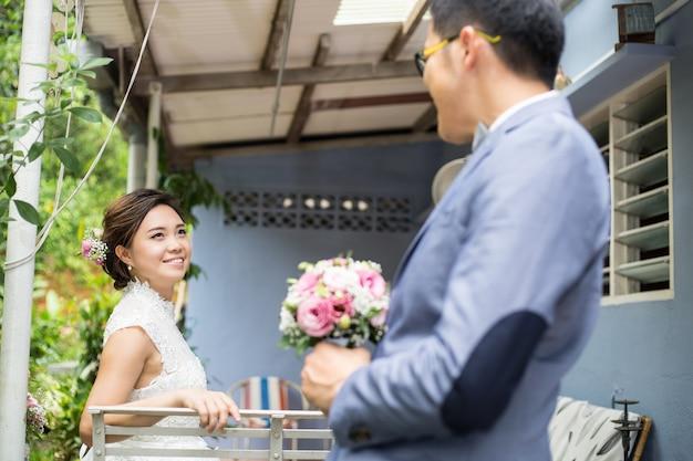 Casamento de casal asiático segurando uma flor e procurando juntos no jardim.