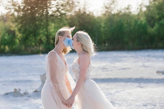 Casamento de casal de lésbicas na areia branca. use máscaras para prevenir a epidemia covid-19