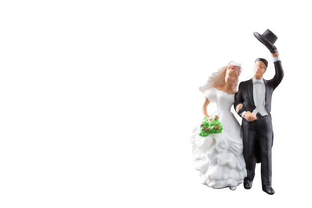Casamento de pessoas em miniatura isolado no fundo branco com traçado de recorte