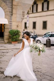 Casamento em florença, itália. mulher afro-americana caminhando com seu vestido de noiva