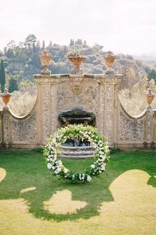 Casamento em uma antiga vila vinícola na toscana, itália. arco redondo de casamento decorado com flores brancas e hortaliças na frente de uma arquitetura italiana antiga.
