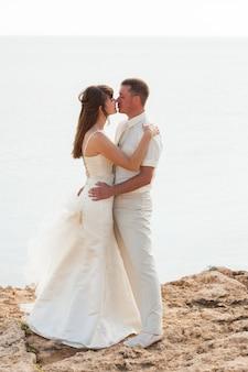 Casamento, linda noiva romântica e noivo beijando e abraçando ao ar livre