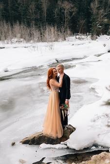 Casamento no inverno, a noiva e o noivo estão parados na margem de um rio congelado e se abraçando.