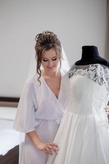 Casamento. noiva em roupão bonito perto do manequim com vestido dentro de casa em casa. estilo de casamento na moda tiro.