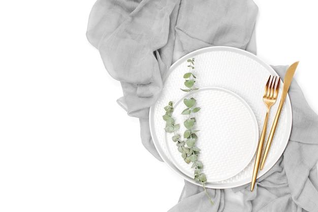 Casamento ou configuração de mesa festiva. pratos e talheres com tecido decorativo cinza sobre fundo branco. belo arranjo.