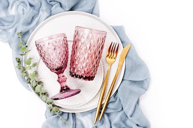 Casamento ou configuração de mesa festiva. pratos, taças de vinho e talheres com tecido decorativo cinza sobre fundo branco. belo arranjo.