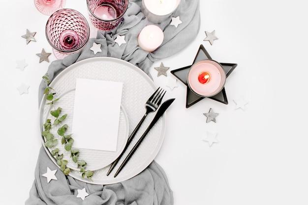 Casamento ou configuração de mesa festiva. pratos, taças de vinho, velas e talheres com tecido decorativo cinza sobre fundo branco. belo arranjo.