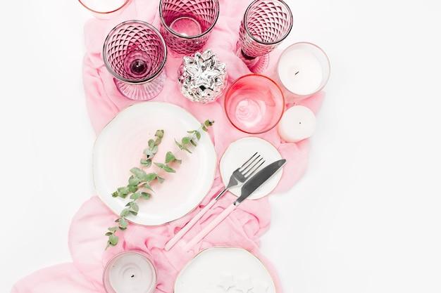 Casamento ou configuração de mesa festiva. pratos, taças de vinho, velas e talheres com têxteis decorativos em fundo branco. belo arranjo na cor rosa