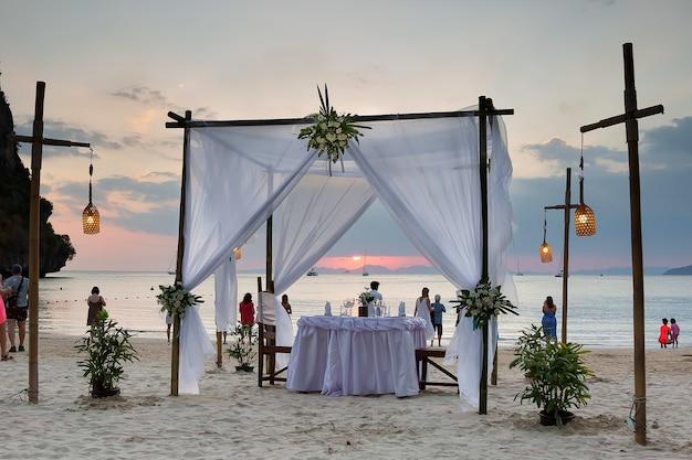 Casamento turistas apreciam a vista do pôr do sol na praia na areia, mesa decorada para um jantar romântico
