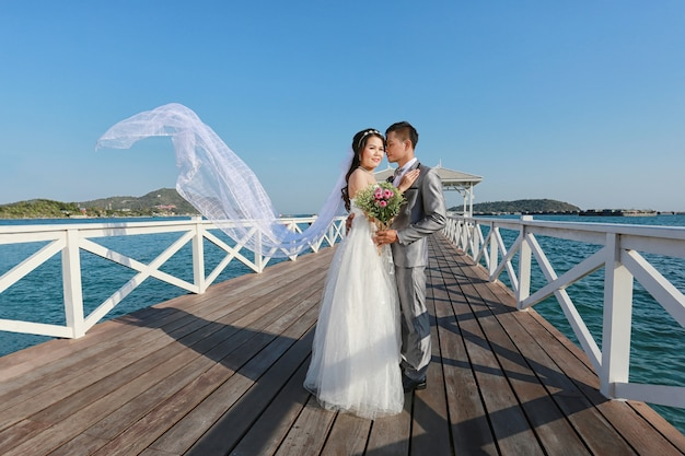 Casamentos tailandeses da fotografia do pre em uma ponte de madeira de atsadang