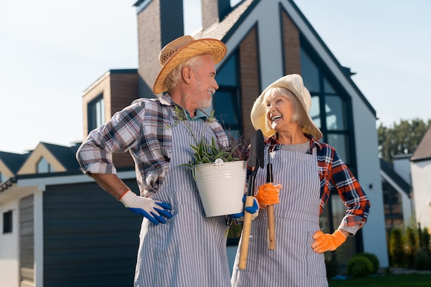 Casarão. casal sorridente e alegre, olhando um para o outro ao lado da casa