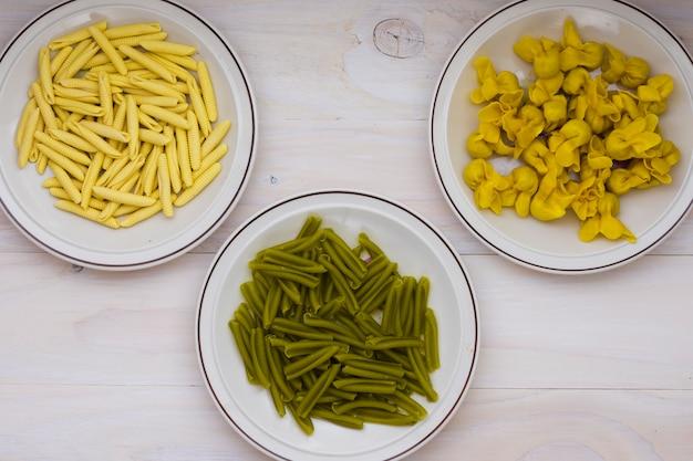 Casarecce de espinafre italiano seco; massa garganelli e tortellini em pano de fundo de madeira